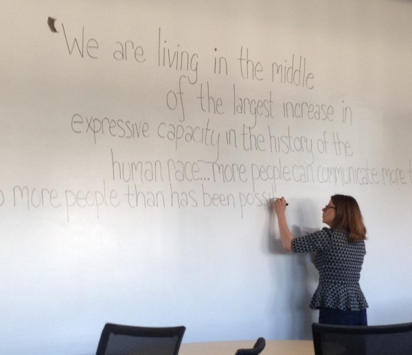 Laura writing Shirky quote on wall